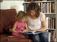 A child reading a book with her mother