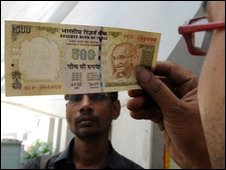 Indian shopkeeper looking at rupee note