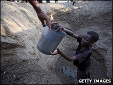 Children from the remote Turkana tribe in Northern Kenya dig a hole in a river bed to retrieve water