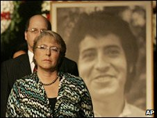 Chilean President Michelle Bachelet stands by a photo of Victor Jara in Santiago