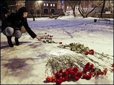 A woman lays flowers outside the Lame Horse nightclub in Perm