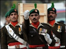 Pakistani soldiers carry the coffin of a colleague killed in the attack on a Rawalpindi mosque