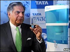 "Ratan Tata, boss of Tata Group, holds a glass of water filled from a ""Swach"" water filter"