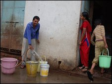 Man filling water buckets in the slums in Bhopal