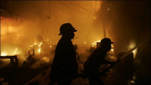 Pakistani firefighters tackling flames at Lahore's Moon Market