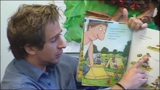Ben Dobson reads a books to a class of children