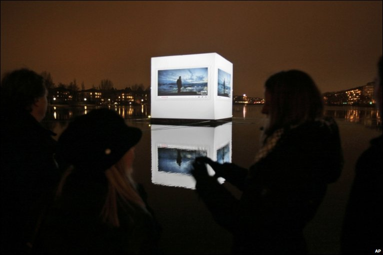 People watch a video on global warming, projected onto a floating cube, on the opening day of the Climate Conference in Copenhagen, Denmark