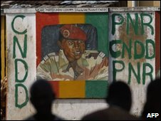 Men sit near a mural depicting Guinean junta leader Capt Moussa Dadis Camara in Conakry, 06/12