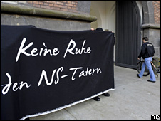"Protesters display a banner reading ""No peace for NS [Nazi] delinquents"" outside the court in Aachen (October 2009)"