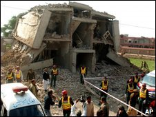 Pakistani volunteers surround the site of a bombing in Multan, Pakistan on Tuesday, Dec. 8, 2009.