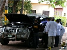 Honduran investigators examine the car in which Gen Arisitides was shot