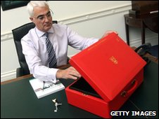 Alistair Darling sits at his desk with a copy of his Pre-Budget Report