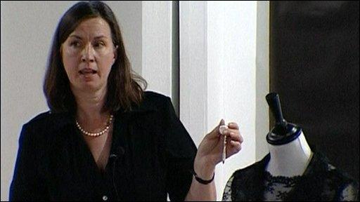 Auctioneer standing next to Hepburn dress