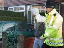 Officer leads arrested suspect