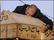 An Iraqi man grieves over his wife's coffin