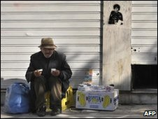 An old man sells tissues outside a store in central Athens