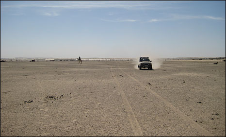 A vehicle drives across the former lake bed