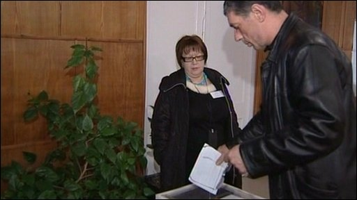 Man putting voting papers in ballot box