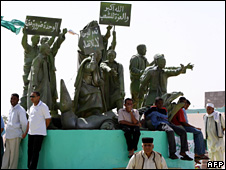 Libyans stand by a statue commemorating a demonstration led by Muammar Gaddafi held in 1961
