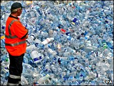 Waste recycling worker standing by a pile of plastic bottles