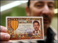 A man shows his symbolic Catalan ID card as he votes in Vilafranca del Penede, Spain, 13 December