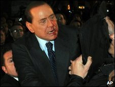 Mr Berlusconi with a bloody face looking around