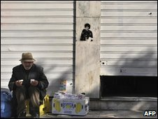 A Greek man sells tissues outside closed store