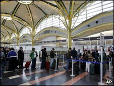Passengers queuing at check-in desk