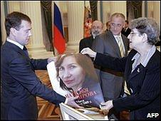 Dmitry Medvedev with poster of rights activist Natalya Estemirova
