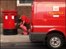 Postman emptying postbox into van