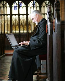 A vicar with a laptop