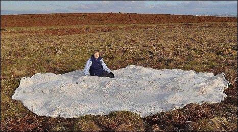 Image shows Swansea Met artist Ann Jordan with the blanket sitting  on top of the Black Mountain