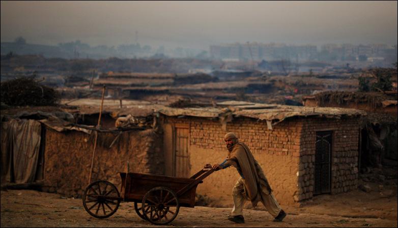 A Pakistani man pushes a cart