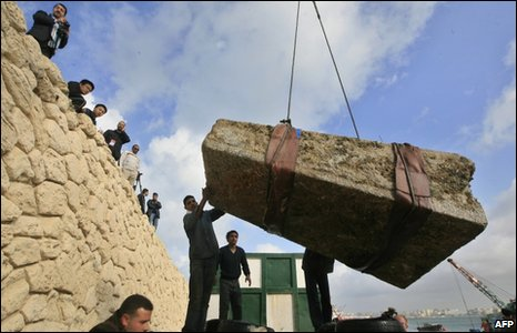 The stone is brought to land in Alexandria with the help of a crane