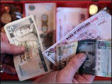 Unidentified hand holding scottish bank notes