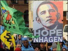 A demontrator holds up a placard featuring Barack Obama during the United Nations Climate Change Conference in Copenhagen