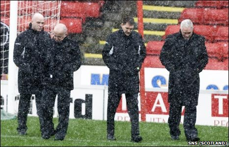 Referee Dougie McDonald (2nd from right) looks over the Pittodrie pitch