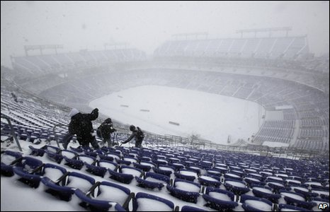 Workers remove snow from the M&T Bank Stadium in Baltimore, 19 December