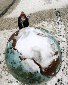 "A young woman giggles beside a snow-covered ""Cool Globe"" part of an exhibition about combating global warming  in Copenhagen, 19-12-2009"