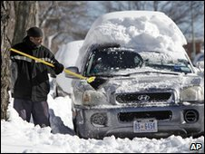A man brushes snow of a car in Washington, 20 Dec