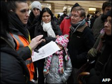 A French railway SNCF company staff member gives information to travellers in the Gare du Nord, Paris