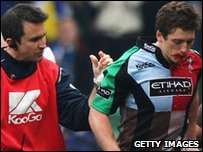 Tom Williams from the Harlequins is led off the field with fake blood coming from his mouth