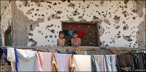 Girls on the balcony of a sdamaged building