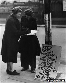A woman signs a public petition against the release from prison of Oswald Mosley