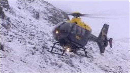 Helicopter flies over snow covered mountain