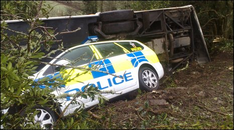 The crashed coach and police car at the scene