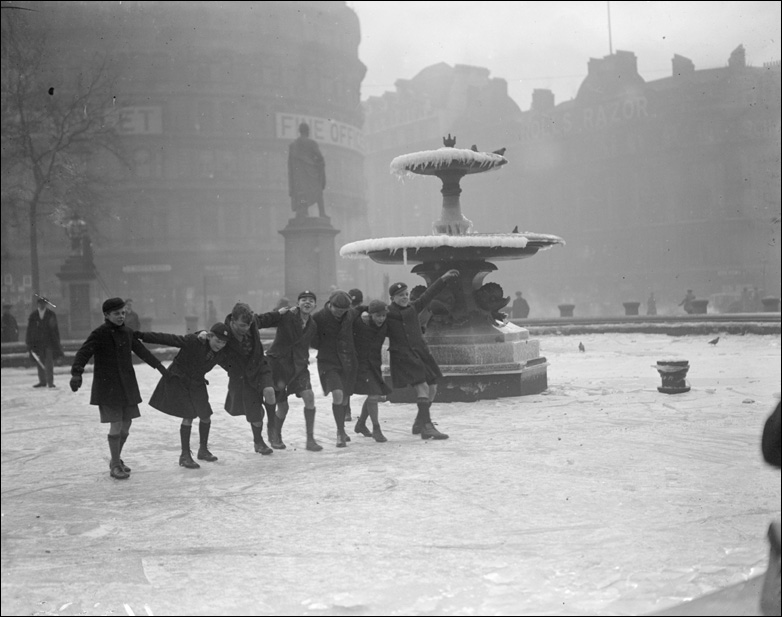 Schoolboys skate on the frozen fountain at Trafalgar Square