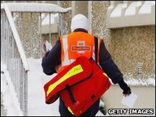 A postman delivers mail in the snow