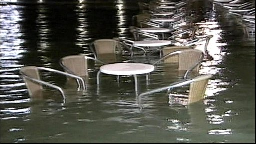 Table and chairs submerged by flood waters in Venice