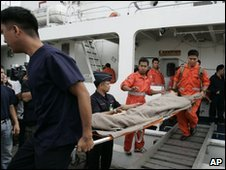A survivor is carried off a boat on a stretcher in Manila, 24 December